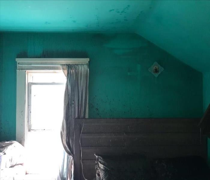 bedroom with blue walls covered in soot from fire and water damage