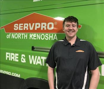 Male with dark hair in front of green van