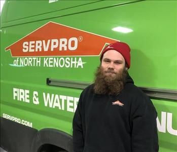 Male employee with beard and red hat in front of green vehicle background