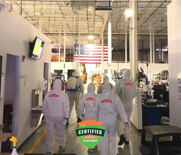 a crew of SERVPRO employees in PPE gear walking inside commercial building